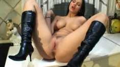 Provoking brunette in black boots shows off her body and masturbates