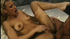 Spreading her body across the bed, a slender blonde has a black guy fucking her twat